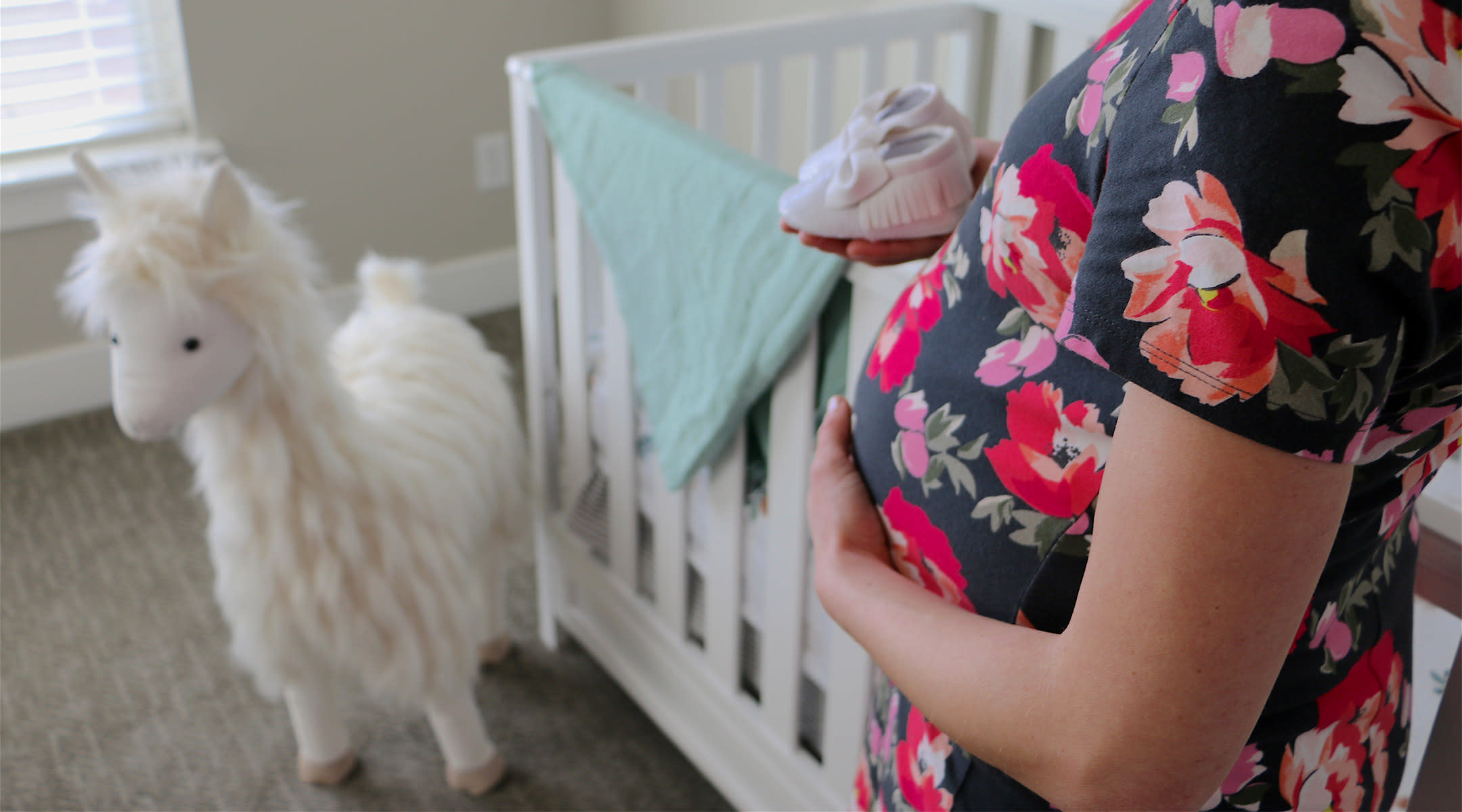 pregnant woman in her nursery holding baby shoes