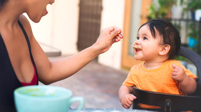 Baby being fed spoonful by his mother.