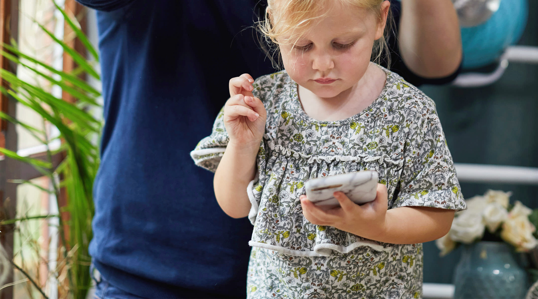 toddler girl playing with mobile phone while dad does her hair