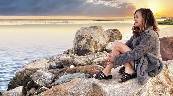 Co-founder of Melissa and Doug, Melissa Bernstein sitting and contemplating on scenic rocks by water.