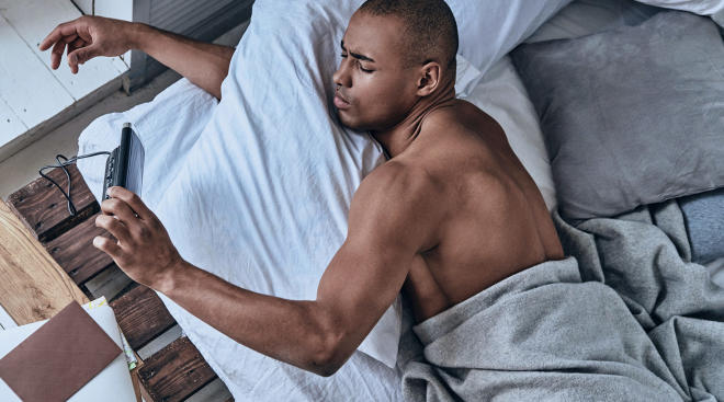 man in bed checking the time