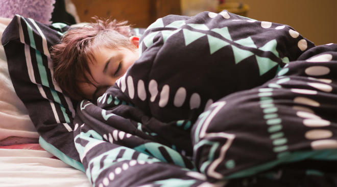 little boy sleeping in bed with pattern blanket