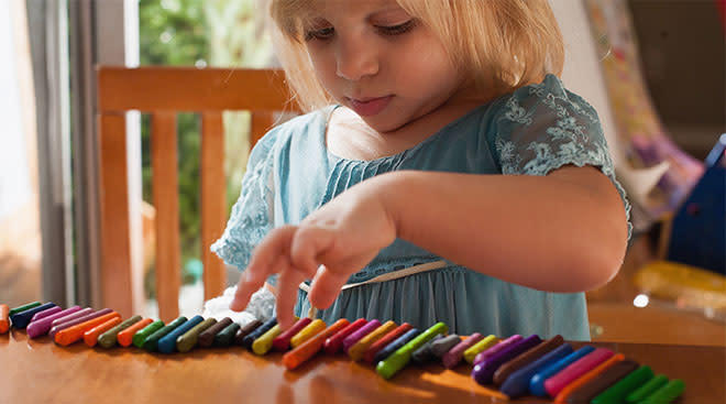 Little girl counting colorful crayons.