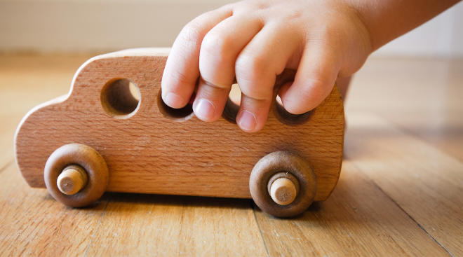 toddler hand playing with wooden toy car