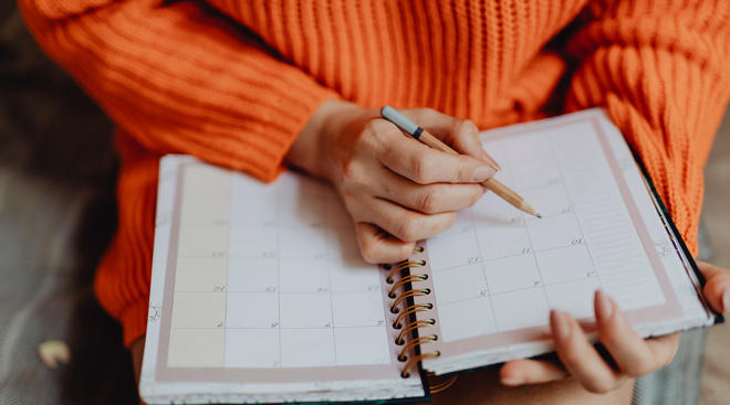 woman in orange sweater making notes in her calendar