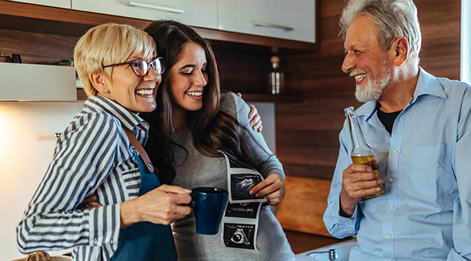Getty Images family looking at sonogram picture together