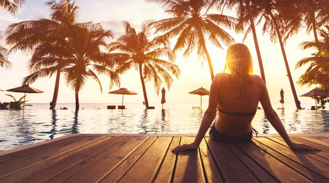 woman relaxing by pool on vacation with palm trees in the background