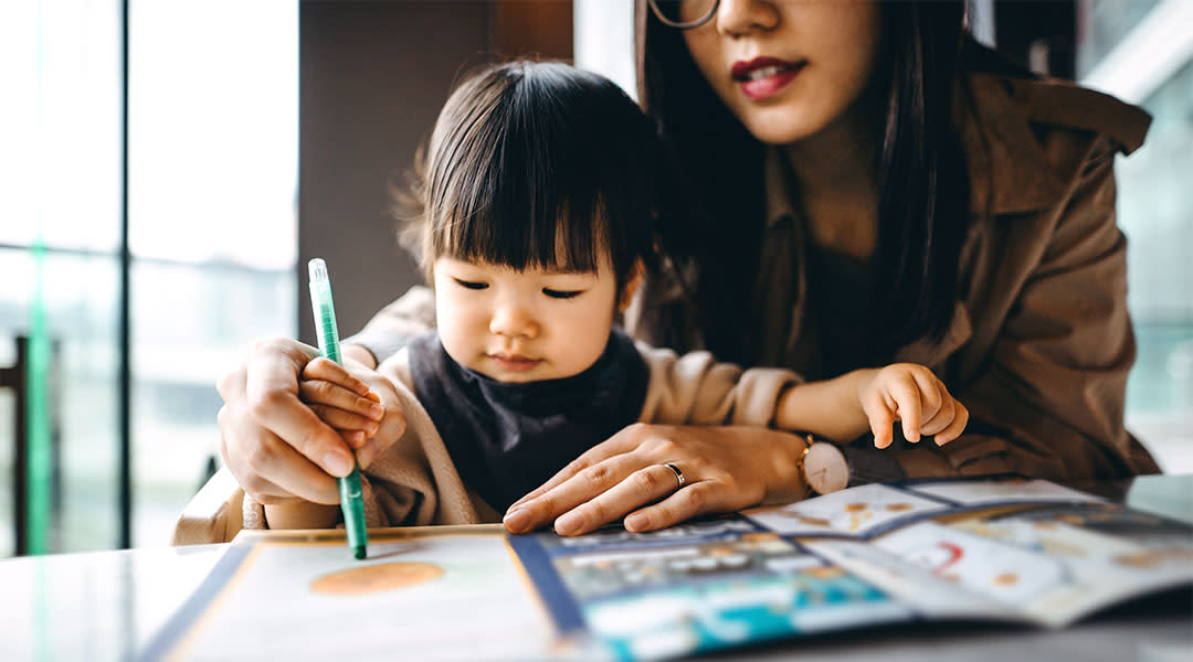 mom helping her toddler draw