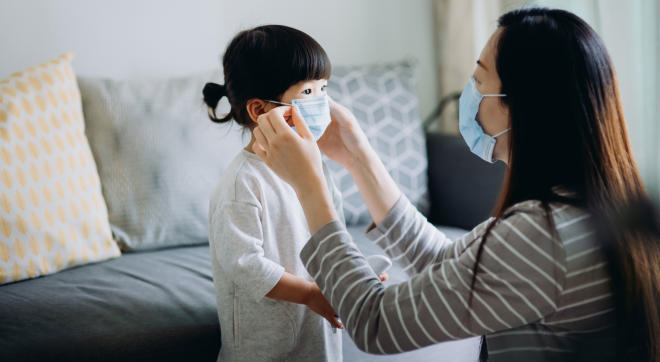 women helps child put on face mask before going outside