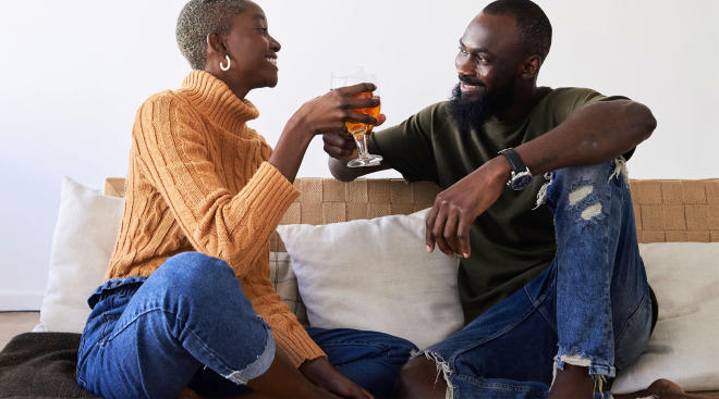 couple drinking beer at home on the couch