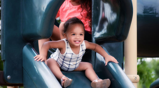 toddler girl sliding down slide at playground with mom behind her