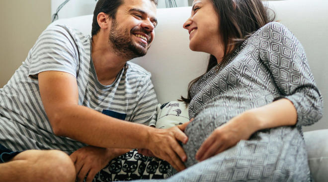 Pregnant woman and her partner together on the couch laughing