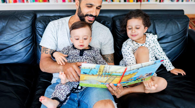 dad reading on the couch to his baby and young daughter