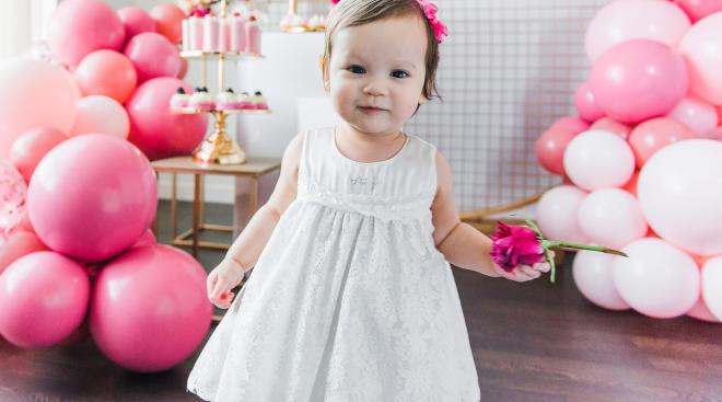little girl in white dress on her first birthday