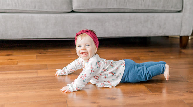 Very happy baby trying to crawl on wooden floor.