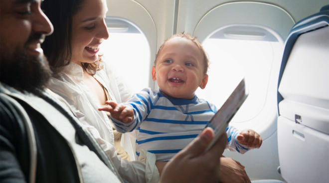 Happy toddler on airplane with relaxed parents