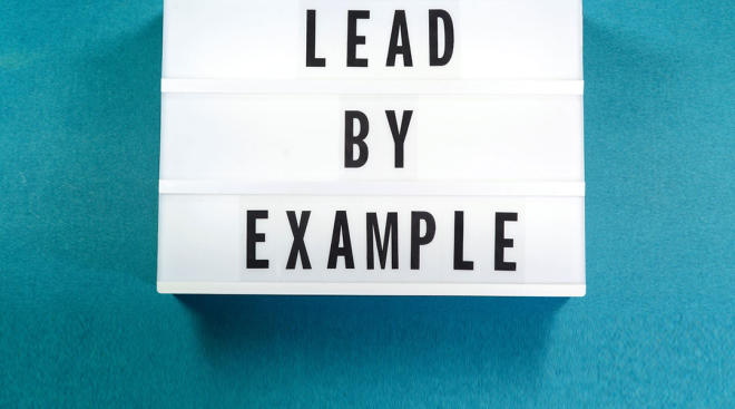 letter board that says lead by example