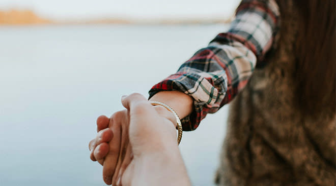 couple walking by water while holding hands