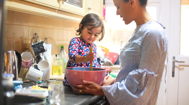 mom with toddler daughter cooking in kitchen