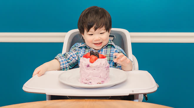 Little boy in a high chair about to have a cake smash for his first birthday.
