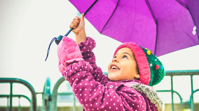 happy little girl looking up and holding purple umbrella