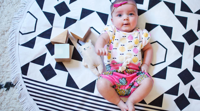 baby on rug surrounded by learning blocks