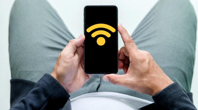 man sits down while looking at wifi signal on phone