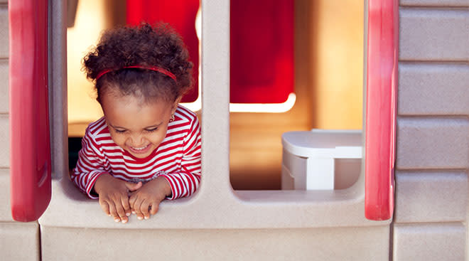 toddler inside playhouse and laughing by window