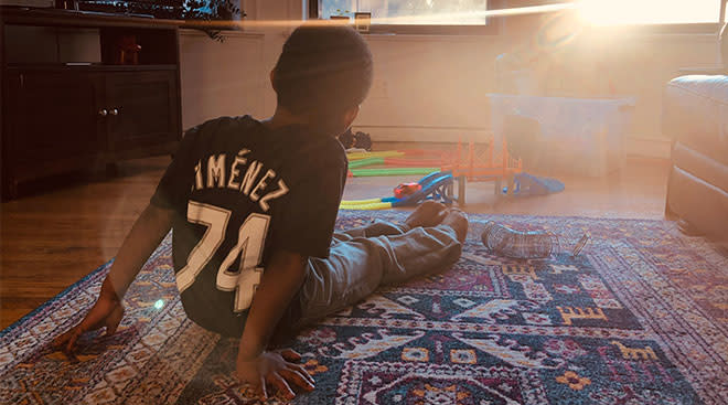 little boy wearing sports t-shirt sits in living room