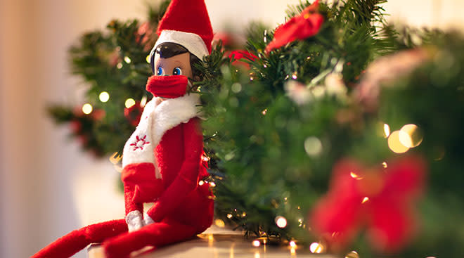 christmas elf on the shelf sitting by greenery and wearing a mask