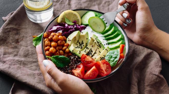 woman's hands eating healthy quinoa bowl