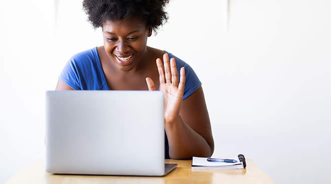woman sits in front of laptop and waves at the screen, talking virtually