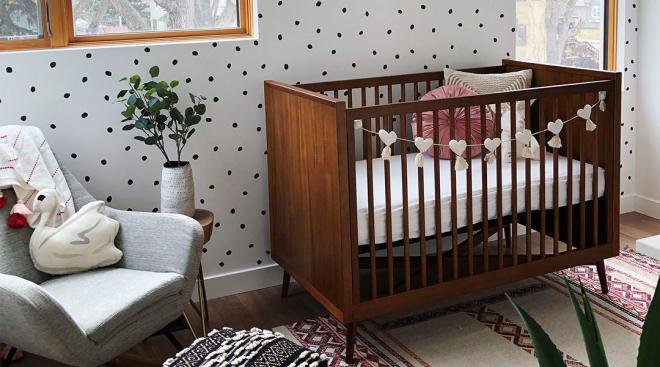 interior shot of baby girl nursery with medium wood crib and polka dot accent wall