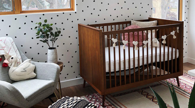 interior shot of baby girl nursery with medium wood crib and polka dot accent wall