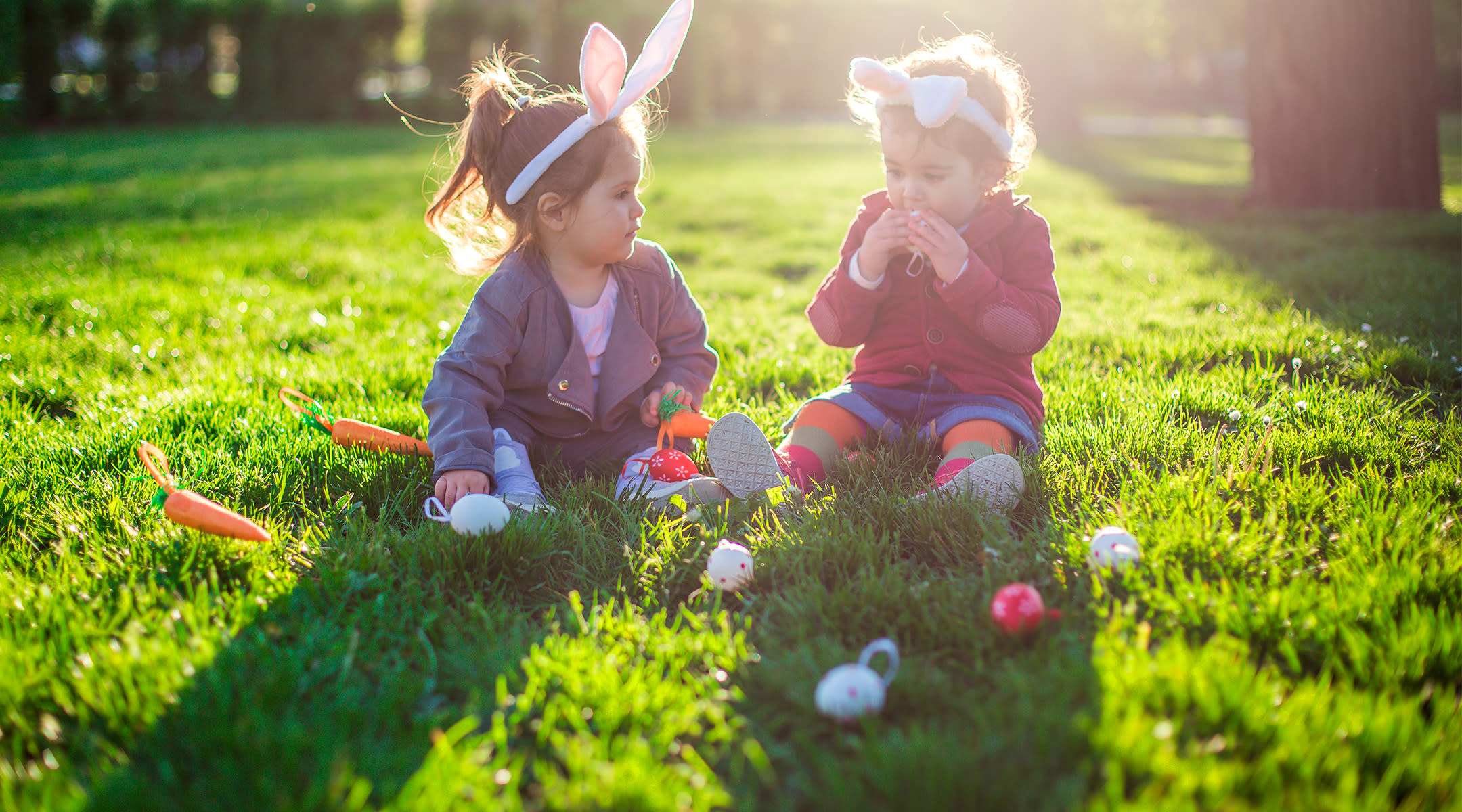 Two toddler girls playing with easter crafts outside on the grass
