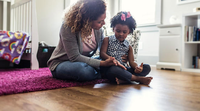 mom sitting and talking with her young daughter on the floor at home