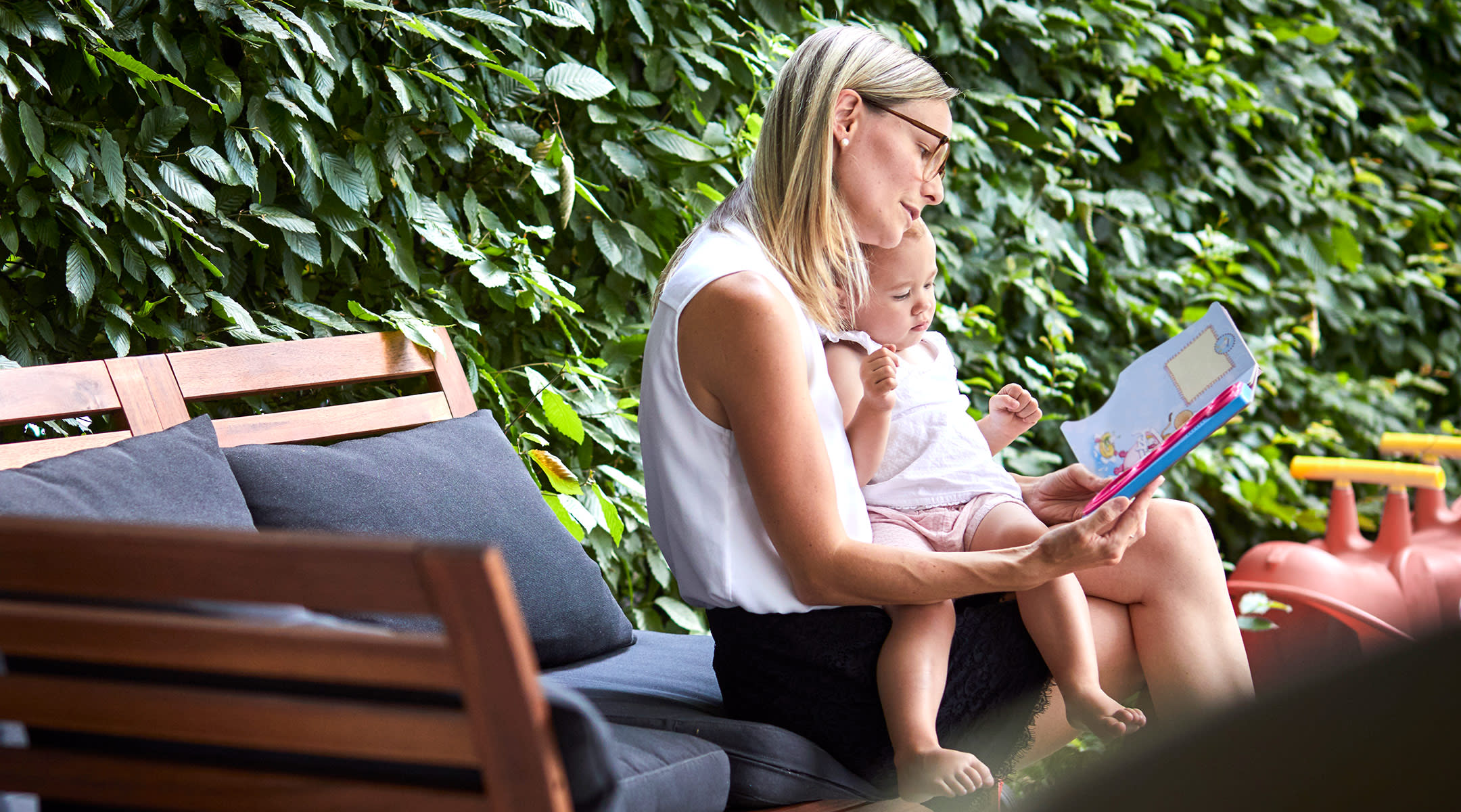 mom reading to her baby in the summer time outdoors