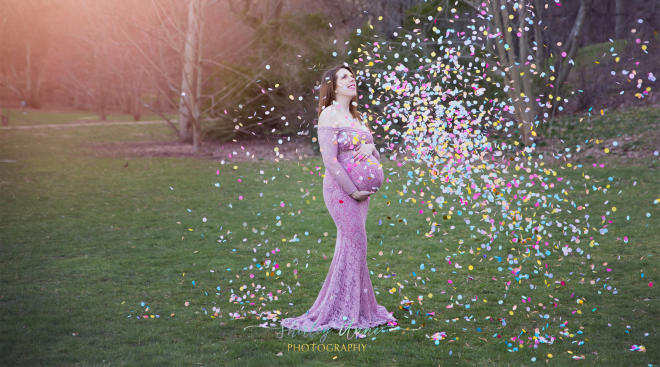 woman pregnant with rainbow baby poses with colorful confetti