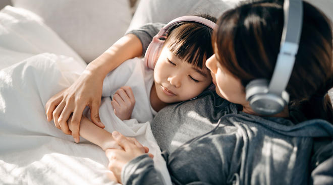 mom and child sit on couch and listen to music together
