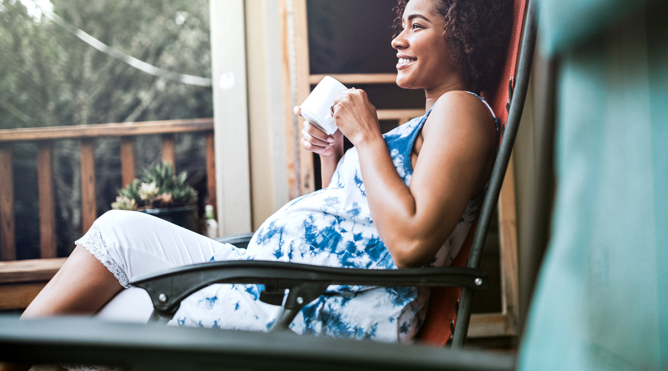 pregnant woman drinking coffee at home laughing