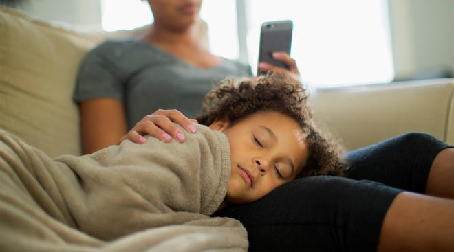 sick child resting on mom's lap