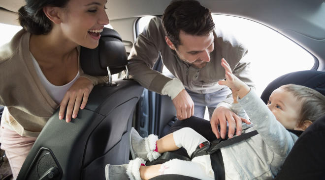 family playing with baby in parked car
