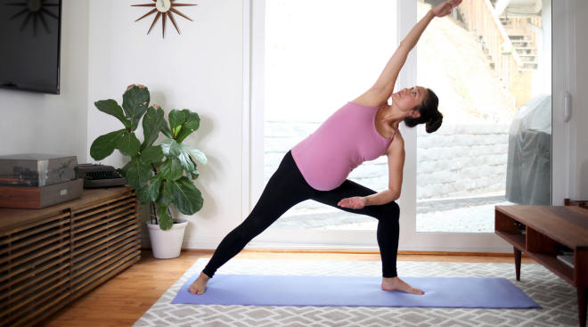 pregnant woman practicing yoga in her living room