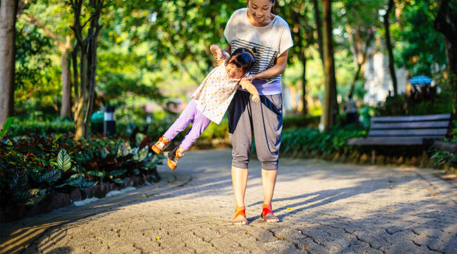 playful mom lifts toddler daughter into the air