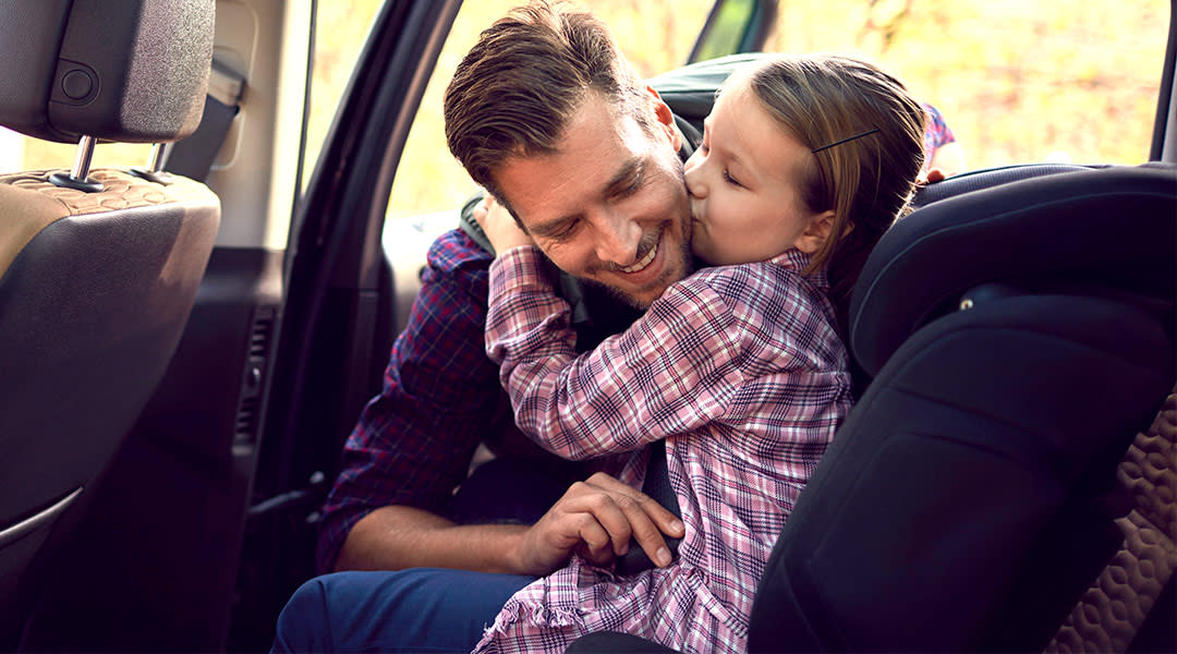 dad straps daughter into her booster seat in the car