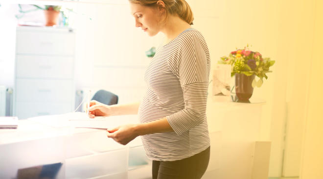 pregnant woman filling out forms at doctor's office