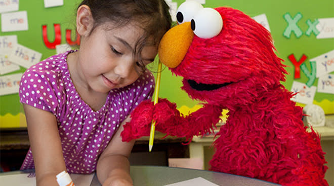 sesame street's elmo plays with little girl