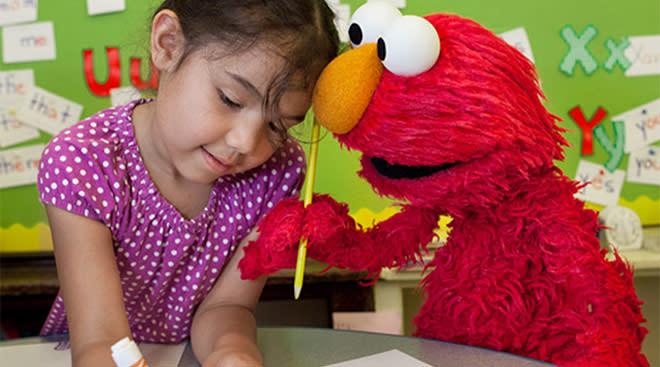 sesame street's elmo plays with little girl