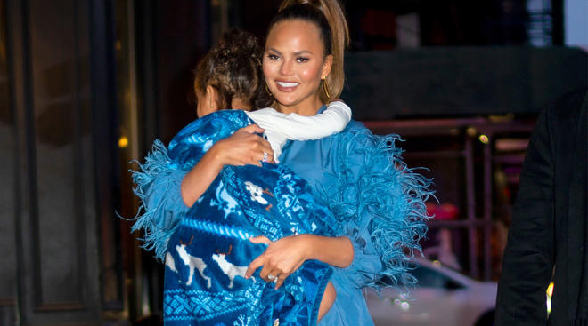 chrissy teigen walking and holding her daughter
