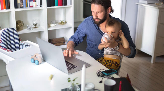 dad holds his son while he stares at computer